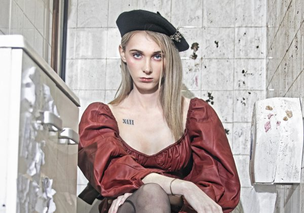 Woman sat in a dirty bathroom. She is wearing a beret on her head and a red dress whilst staring directly into the camera