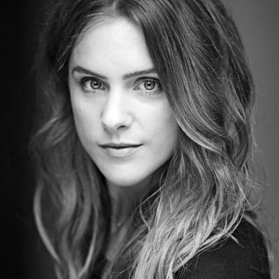 A black and white headshot of Kelly Gough. Kelly looks into the camera with a neutral expression.